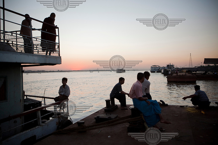 Passengers on a boat and people waiting on the quay side watch the sun set in Yangon.