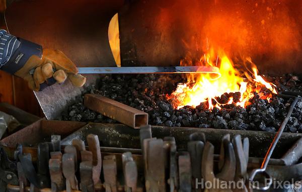 Nederland Broek op Langedijk 2015 . Nationale Folkloredag, met veel mensen in Nederlandse  klederdracht, bij Museum de BroekerVeiling. De Broekerveiling is de oudste doorvaarveiling ter wereld. Smid aan het werk in de smederij