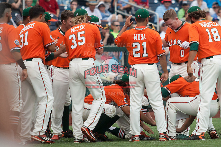 Miami Hurricanes teammates greet catcher Zack Collins (0) after his first inning home run against the UC Santa Barbara Gauchos in Game 5 of the NCAA College World Series on June 20, 2016 at TD Ameritrade Park in Omaha, Nebraska. UC Santa Barbara defeated Miami  5-3. (Andrew Woolley/Four Seam Images)