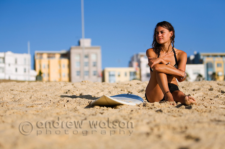 A young surfer sits on the beach at Bondi on Sydney's eastern beaches.  Bondi Beach, Sydney, New South Wales, AUSTRALIA.