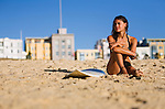 A young surfer sits on the beach at Bondi on Sydney's eastern beaches.  Bondi Beach, Sydney, New South Wales, AUSTRALIA.