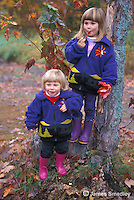 Little sisters in matching sweaters standing by a tree in fall
