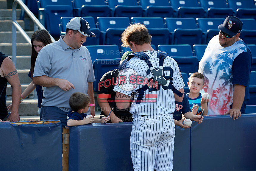 Staten Island Yankees catcher Josh Breaux (28) signs autographs for fans after a game against the Lowell Spinners on August 22, 2018 at Richmond County Bank Ballpark in Staten Island, New York.  Staten Island defeated Lowell 10-4.  (Mike Janes/Four Seam Images)