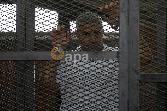 Defendants in the Marriott terror cell case in Cairo stand in cages in an Egyptian courtroom, in Cairo on May 22, 2014. A total of 20 defendants in the case are charged with harming Egypt's national interests by spreading false news and assisting or belonging to a terrorist organization, but 12 are being tried in absentia. Photo by Mohammed Bendari