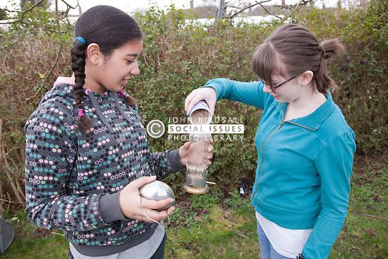 Girls topping up wild bird feeder.