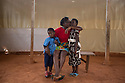"""Cameroon - Yaoundé - Nancy Joyce Fanke, 27 years old sits next to her children. Fanke works as a waitress in a night bar and has two children she has raised alone since May 2014, when her husband David Fongang left. """"Yes, I am angry, because I spent so much money and he failed so many times"""" she admits sincerely, while caressing her daughter's hair. """"It's me alone who has to feed and fund the education of the children."""" In these years Fongang tried to enter Europe several times, first by climbing the barrier between Morocco and the Spanish enclaves of Ceuta and Melilla and then by trying to cross the Mediterranean, from Libya to the Italian island of Lampedusa. His failures have taken a toll not only on the family's finances, but on the young man's psyche as well. """"It was extremely hard for him to see his friends pass, while he was always rejected. He also saw a lot of his comrades dying during the attempted crossings."""""""