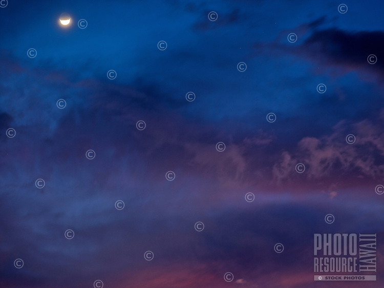 A half moon with pink clouds and blue sunset sky on Maui.