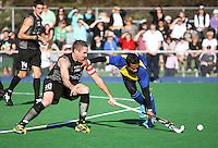 NZ captain Phil Burrows is tackled by his Malaysian counterpart Mohd Madzli Ikmar Mohd Nor during the international hockey match between the New Zealand Black Sticks and Malaysia at Fitzherbert Park, Palmerston North, New Zealand on Sunday, 9 August 2009. Photo: Dave Lintott / lintottphoto.co.nz