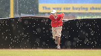 July 17, 2009: A member of the Potomac Nationals grounds crew helps pull the tarp during a rain delay prior to a game against the Kinston Indians at G. Richard Pfitzner Stadium in Woodbridge, Va. Photo by:  Tom Priddy/Four Seam Images