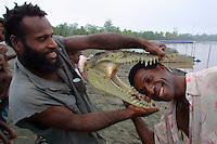 East Sepik Province. Village Mumeari on Korosameri River. Leonhard (r.) presenting the head of a 12 feet long salt water crocodile he just killed.