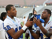 Armwood Hawks defensive lineman Byron Cowart #58 takes the championship trophy from teammate Keionne Baines #32 after the Florida High School Athletic Association 6A Championship Game at Florida's Citrus Bowl on December 17, 2011 in Orlando, Florida. Armwood defeated Miami Central 40-31. (Photo By Mike Janes Photography)