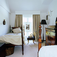 In the twin-bedded guest room the sconce is a Darryl Carter design and the unusual horn chair is an antique