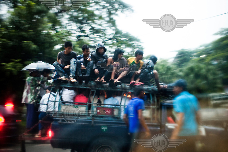 A truck laden with people, including some sitting on the roof, travels along a road in Yangon.