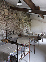 The children's bedroom is more like a dormitory with a row of matching wrought-iron beds against an exposed stone wall