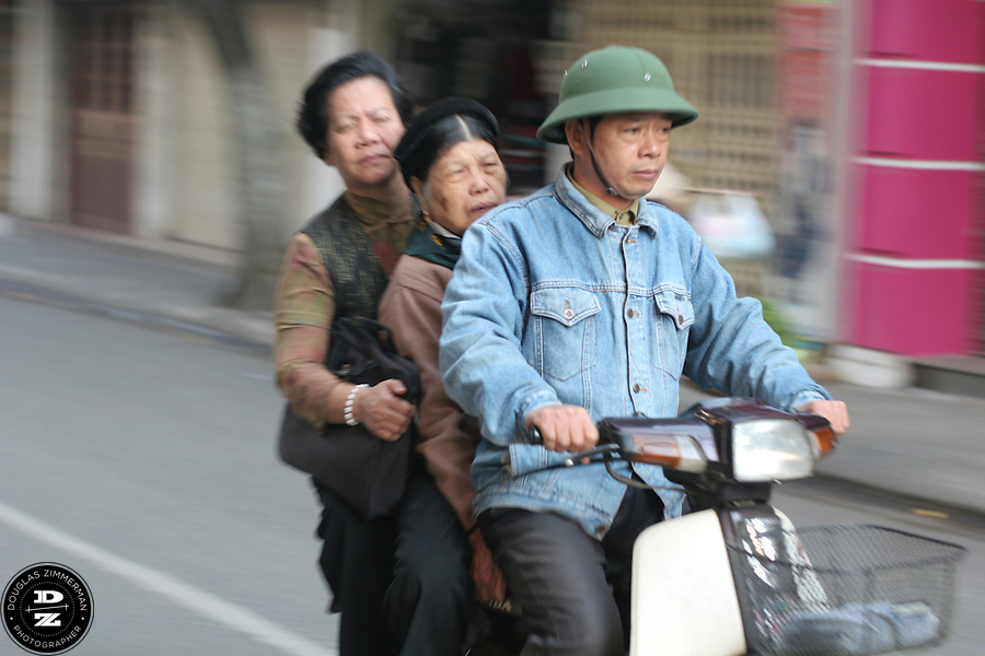 A motorbike with three passengers races down a street in the Old Quarter of Hanoi, Vietnam.  Photograph by Douglas ZImmerman