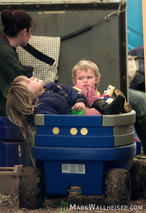 "Juliette Crowell  (foreground), 2 year old from Frankfort, KY, and 20 month old Amelia Winter of Newnan, Ga. share a utility wagon in one of the three stables at the Red Hills Horse Trials in Tallahassee, Florida March 7, 2003.  Crowell's mom, Dorothy Crowell said that the wagon is used to haul everything from feed and water to babysitting the kids.  ""It comes in really handy,"" said Crowell. (Mark Wallheiser/TallahasseeStock.com)"