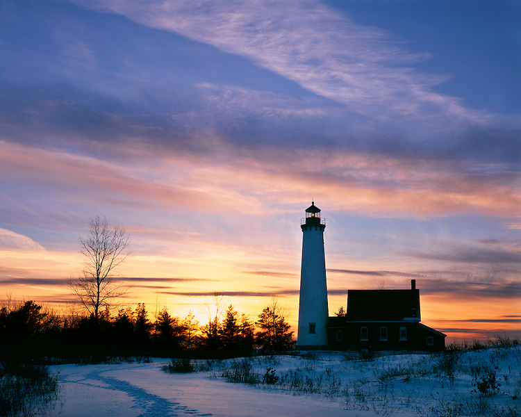 Winter sunset light on Tawas Point Lighthouse on Lake Huron; Tawas Point State Park, MI