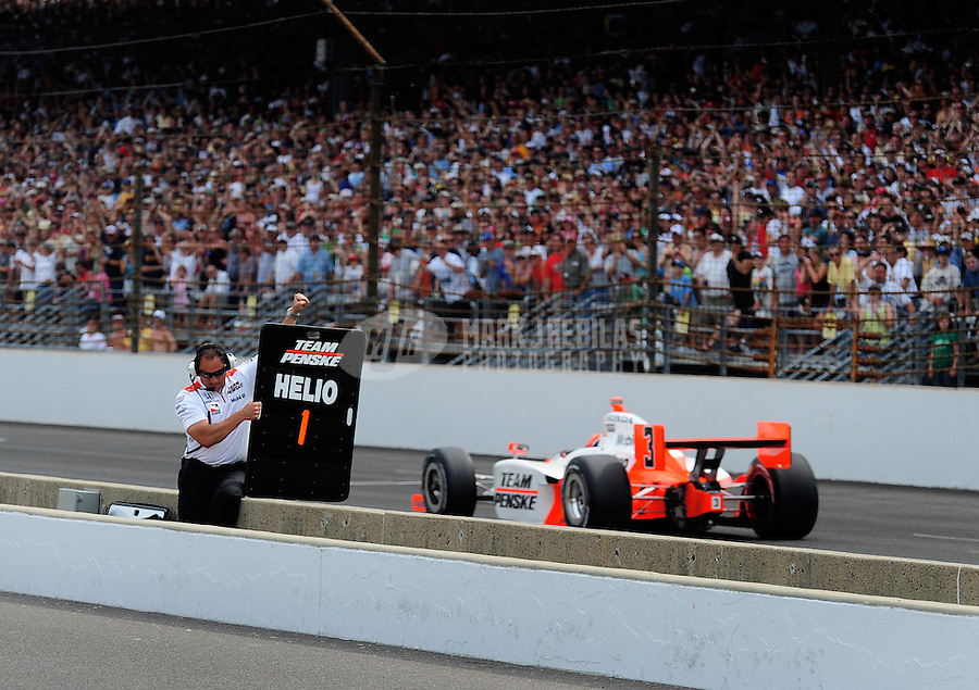 May 24, 2009; Indianapolis, IN, USA; IRL driver Helio Castroneves passes a crew member indicating one lap to go during the 93rd running of the Indianapolis 500 at Indianapolis Motor Speedway.  Mandatory Credit: Mark J. Rebilas-
