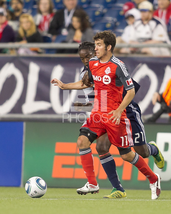 Toronto FC midfielder Nathan Sturgis (11) dribbles as New England Revolution midfielder Shalrie Joseph (21) pressures. In a Major League Soccer (MLS) match, the New England Revolution tied Toronto FC, 0-0, at Gillette Stadium on June 15, 2011.