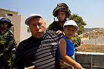 A palestinian demonstrator carries his young son after being arrested by Israeli soldiers during a non-violent demonstration in the West Bank village of An Nabi Salih near Ramallah on 09/07/2010.