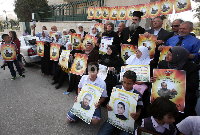 Palestinians hold pictures of prisoners held in Israeli jails during a sit-in outside the Red Cross offices in Jerusalem, in solidarity with hunger-striking detainees held by Israel to demand their release from detention without trial,on march 14, 2013. Photo by Mahfouz Abu Turk