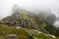 Peru, Machu Picchu.  Early Morning Clouds Engulf the Ruins.