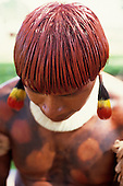 Posto Leonardo, Xingu, Brazil. Man with hair dyed with red Urucum paste and colourful feather ear rings.