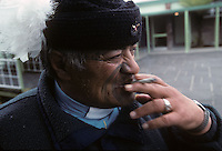 A Maori priest takes a drag of his cigarette in Rotarua, New Zealand in 1995.