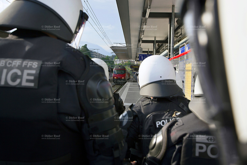 Switzerland. Canton Ticino. Lugano. Railway station. A group of police officers from TPO (Transport Police). The policemen wear the special riot police black uniforms and helmets. They are standing on the platform and wait for the arrival of the FC Luzern football club's supporters in a chartered train. TPO (Transport Police) is the Swiss Federal Railways Police. Swiss Federal Railways (German: Schweizerische Bundesbahnen (SBB), French: Chemins de fer fédéraux suisses (CFF), Italian: Ferrovie federali svizzere (FFS)) is the national railway company of Switzerland. It is usually referred to by the initials of its German, French and Italian names, as SBB CFF FFS. 2.06.2017 © 2017 Didier Ruef