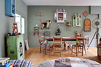 A children's playroom decorated in a sage green colour and a wooden floor. The room is furnished with a metal table and 18th century Scandinavian chairs. A collection of vintage items are displayed on the wall.