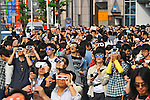 Tokyo, Japan - May 21: People stopped to look up at an annular solar eclipse at Shinjuku Statation, Shinjuku, Tokyo, Japan in a morning on May 21, 2012. Last time it was seen at mainland Japan was 129 years ago, and people tried to look at the solar event with special glasses on.