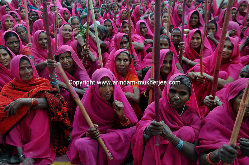 Gulabi Gang members with sticks during a meeting at Fatehepur in Uttar Pradesh. Sampat Pal Devi the commander of Gulabi Gang fights for women empowerment, justice and rights among the poor people of Bundelkhand region of Uttar Pradesh. Sampat Pal Devi comes from a poor family in Bundelkhand - the poorest region of India. The region is fraught with abject poverty, gross under development, lack of law and order, and stark casteism in which the Brahmins and other higher caste people treat their low caste brethren with disdain. Out of such situation when Sampat Pal Devi decided to speak up for the poor, she has been winning heart felt gratitude of the poor as well as enmity of the high caste people and grudging respect of the law enforcement officials who used to be largely inactive in these badlands of North India. Initially, she began with helping distressed women - victims of domestic violence and dowry system, but soon started getting other cases of nature of land dispute and under development. She emerged as a fiery leader in 2007, when she beat up the OC of the local police station while demanding release of a dalit woman kept locked up in the cell for thirteen days without being charged with a case.Today, she has a huge fan following of some 25 hundreds of thousands of women (spread across 8 districts of the state of UP) who have come to be known as Gulabi Gang or Pink Vigilante Women for their vibrant pink sarees - the costume of the gang; and fiery nature of dealing with injustice. When verbal negotiations for justice fail they resort to beating up. Sampat Devi is viewed as a messiah with the promise of bringing back law and order for the poor, in these mafia troubled areas. Today, perpetrators are simply scared of her as she does not hesitate to challenge law and order and even system - to win justice for the poor. More complaints related to domestic violence and other problems are registered now with the police than they ever used to be. She being one of the