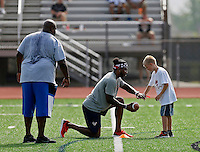 Former Ohio State Buckeye Braxton Miller shows Carson Lykins of Westerville how to take snap as a quarterback during the Braxton Miller football two day camp at Worthington Kilbourne High School on June 13, 2016.  (Kyle Robertson / The Columbus Dispatch)