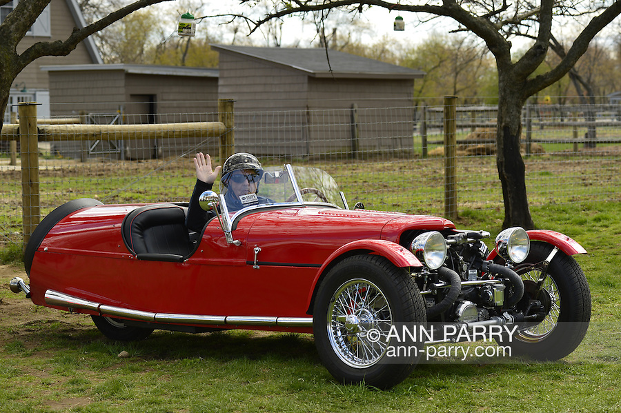 Floral Park, New York, U.S. - April 27, 2014 - Owner STEVE KAPLAN waves good-bye as he is about to drive away in his red BRA CX3, a custom Beribo Replica Automobiles kit vehicle with three wheels, at the 35th Annual Antique Auto Show at Queens Farm. The DMV, Department of Motor Vehicles, registered it as a 2009 Custom Motorcycle.