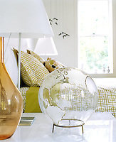 On the bedside table light is reflected from a transparent glass globe next to the lamp