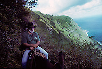 "Eldon ""Buzzy"" Sproat brings up the tail end of a tour group en route to the leper colony on the Kalaupapa peninsula in 1995. Sproat helped create the Kalaupapa mule tours on Molokai. He passed away on June 14, 2014 at age 76."