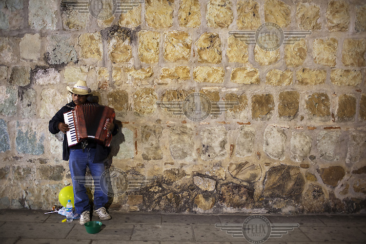 A busker plays an accordion.