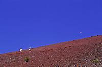 Hiking on the red moonlike landscape of Sliding Sands Trail against a brilliant blue sky in Haleakala National Park on Maui.