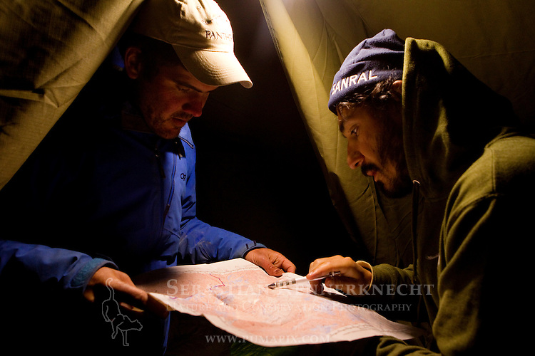 Snow Leopard (Panthera uncia) biologists, Shannon Kachel and Khalil Karimov, looking at map of study area, Pikertyk, Tien Shan Mountains, eastern Kyrgyzstan