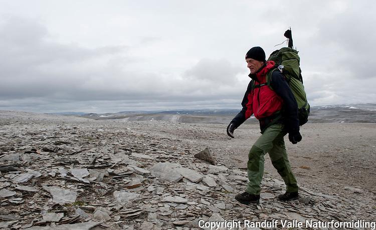 Mann går til fots i goldt fjellterreng på Nordkynn. ---- Man hiking in rocky terrain.