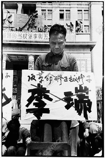 "Forced to stand on chairs in front of the North Plaza Hotel, the seven secretaries of the Heilongjiang Party committee are denounced for ""carrying out Liu Shaoqi's revisionist line."" Each wears a placard with his name crossed out and a description of his alleged crime. Here, Li Rui. Harbin, 27 April 1967"