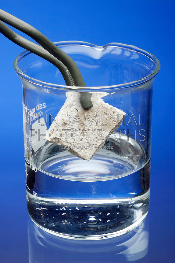 LIMESTONE REACTS TO HCL<br /> Calcite in Limestone Reacts With HCl<br /> Limestone rock is placed in beaker of HCl acid using pair of forceps. Calcite within the limestone reacts with the acid, forming calcium chloride and carbon dioxide, which appears in the solution as bubbles.