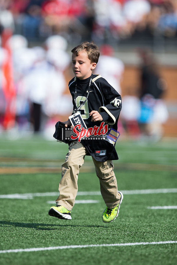 "Deac Haas runs off the field carrying the kick-off tee as the ""Kick-off Kid"" as the Wake Forest Demon Deacons played host to the North Carolina Tar Heels at BB&T Field on October 24, 2015 in Winston-Salem, North Carolina.  The Wolfpack defeated the Demon Deacons 35-17.   (Brian Westerholt/Sports On Film)"