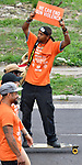 Cornell McKay, a survivor of a random drive-by shooting in 2010, holds a sign aloft as he rides his skateboard along with walkers in the Wear Orange Day March against gun violence on Saturday June 2, 2018. June is National Gun Violence Awareness Month.<br /> Photo by Tim Vizer