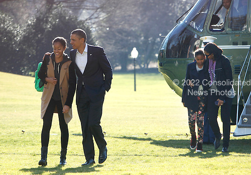 United States President Barack Obama walks with daughter Malia as the First Family returns to White House from their Hawaiian vacation on Sunday, January 6, 2013.  First lady Michelle Obama walks with daughter Sasha from Marine One to the White House. .Credit: Dennis Brack / Pool via CNP