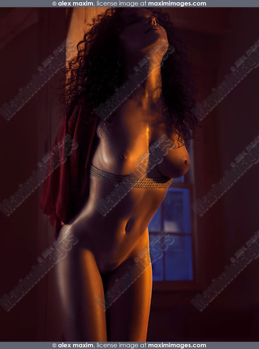 Beautiful nude woman standing naked by a wooden pillar tied with bondage ropes in dim dramatic light with glittering skin