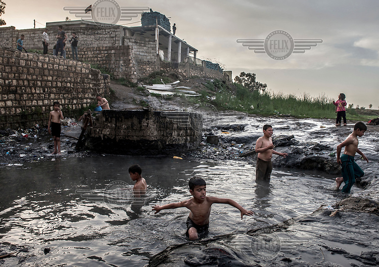 Boys play in the natural hot springs in Hamam al Alil, which was recaptured from ISIS militants at the end of 2016.