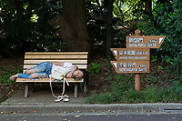 Awoman sleeps on a park bench in Shinjuku Gyo-en Park in Shinjuku, Tokyo, Japan Tuesday June 26th 2018