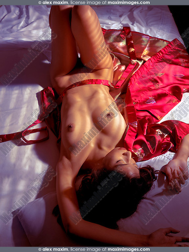 Sexy asian woman lying naked on red kimono in bed in dim light