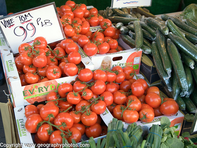 Vine tomatoes for sale on market stall priced in sterling and pounds weight